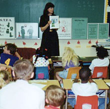 Teacher with Kelly Bear CARES program posters